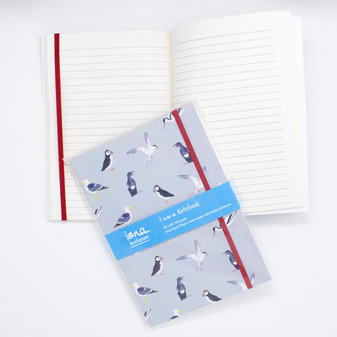 A notebook with elasticated enclosure with a sea birds design showing open pages