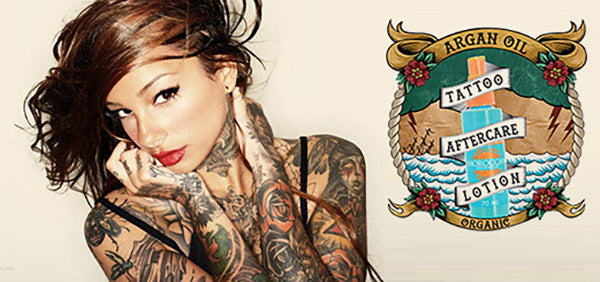 Tattooed girl with argan oil bottle