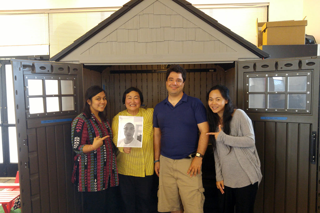 Striivers Beleena Vera, Tammi Goda, Dustin Martin, and Helen Xiong (and Christopher Russell, by proxy) pose in front of The Shed.