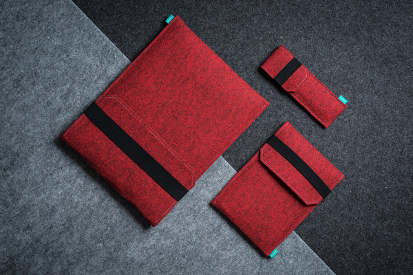 Red felt cases with flap and elastic band for Macbook Pro, iPad and pencils laying on layers of light and dark gray felt - designed and handmade by Gopher