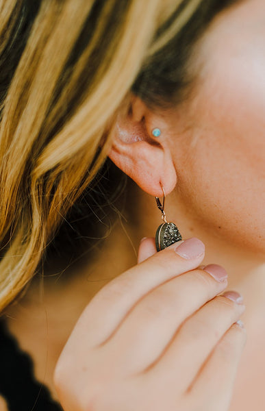 Black druzy oval gemstone earrings with rose gold metals by J'Adorn Designs handcrafted jewelry, worn by a boudoir model in black lace with long blonde hair