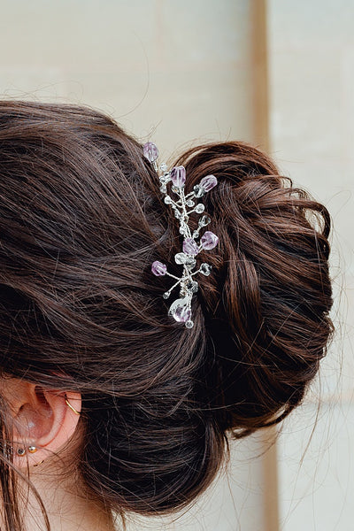 Amethyst and silver hair comb with blue and grey crystal branches modeled in a loose bun bridal updo. Colorful bridal headpiece in purple and cool colors, handcrafted hair accessories by J'Adorn Designs jewelry artisan Alison Jefferies.