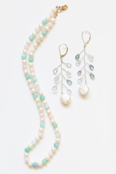 One handcrafted strung pearl necklace in rainbow pastel colors, made with white freshwater pearls and beryl beads with a 14k gold filled clasp. The pearl necklace is paired with delicate aquamarine and coin pearl vine earrings.Artisan jewelry and luxury bridal accessories handmade in Maryland by Alison Jefferies of J'Adorn Designs.