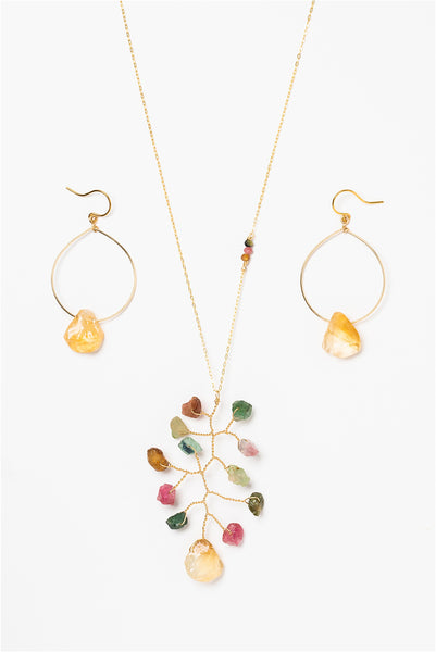 Long asymmetrical necklace with rough rainbow tourmaline and citrine gemstones in a wire wrapped branch design. Coordinated gold hoop earrings with rough citrine drops. Gold jewelry set made by J'Adorn Designs artisan Alison Jefferies of Baltimore, MD.