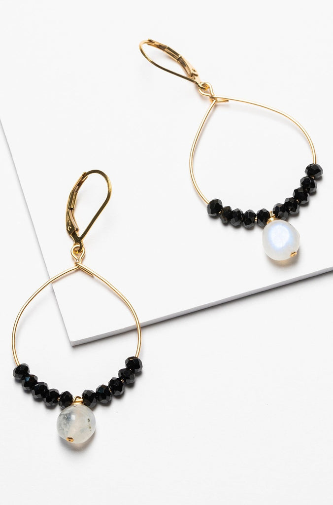 Black and gold handcrafted hoop earrings for sale. A pair of delicate gold hoops with black spinel and moonstone bead accents for luxury fashion or a jewelry gift idea. Artisan jewelry and luxury bridal accessories handmade in Maryland by Alison Jefferies of J'Adorn Designs.