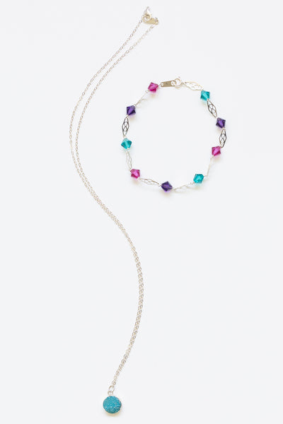 Photo of a necklace and bracelet jewelry set in mermaid colors. A delicate bezel set druzy necklace is paired with a delicate sterling silver link bracelet with crystal beads in jewel tones. Artisan jewelry and luxury bridal accessories handmade in Maryland by Alison Jefferies of J'Adorn Designs.