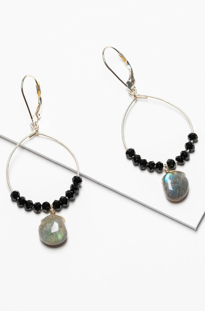 A pair of black and silver hoop earrings with black spinel and iridescent grey labradorite drops. Celestial inspired jewelry for luxury fashion or a jewelry gift idea. Artisan jewelry and luxury bridal accessories handmade in Maryland by Alison Jefferies of J'Adorn Designs.