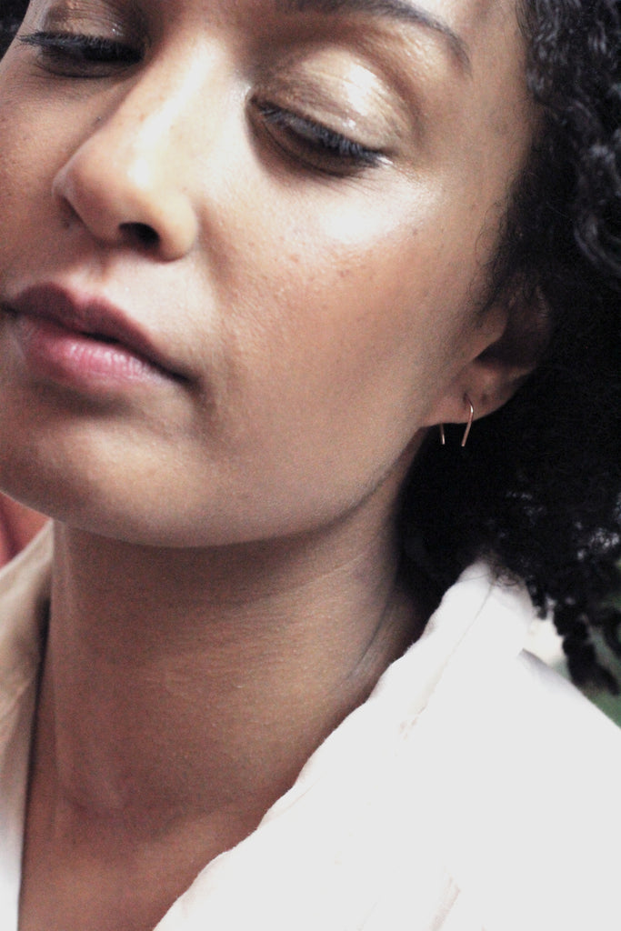 Artisan crafted Hook mini earrings from recycled gold by M of Copenhagen on model up close