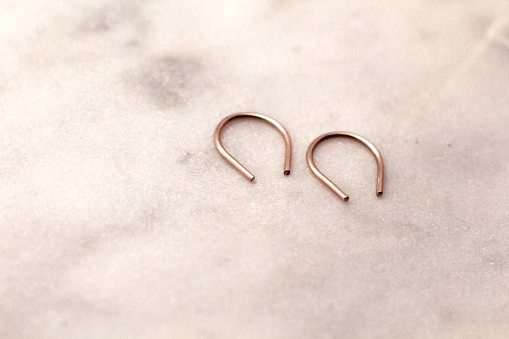 Artisan heirloom jewellery Hook mini earrings by M of Copenhagen from 9 ct red gold on marble background
