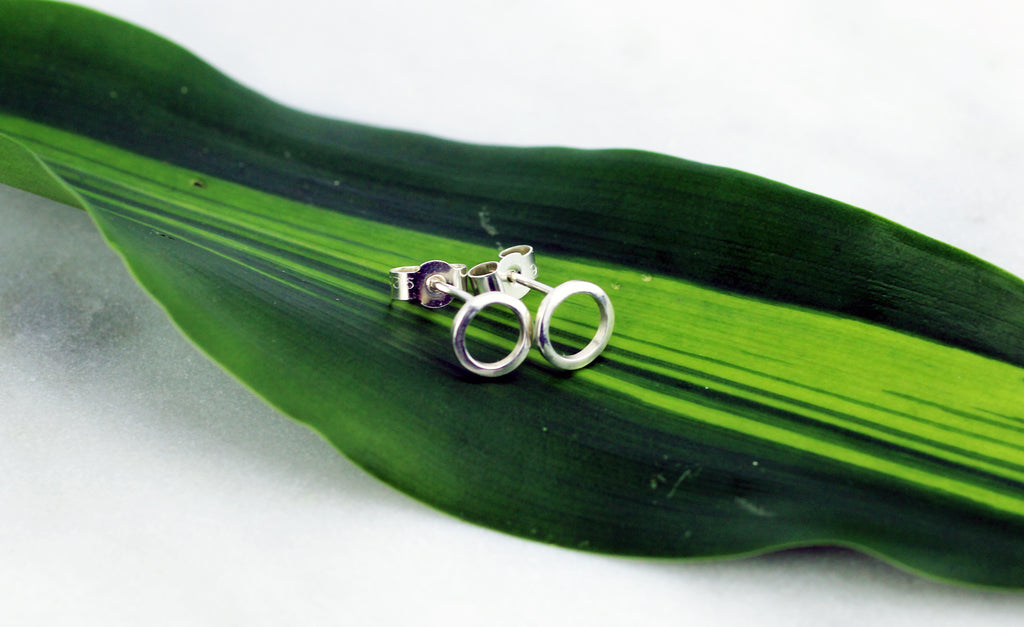 Continuum earrings by M of Copenhagen made from recycled silver flatlay on a leaf