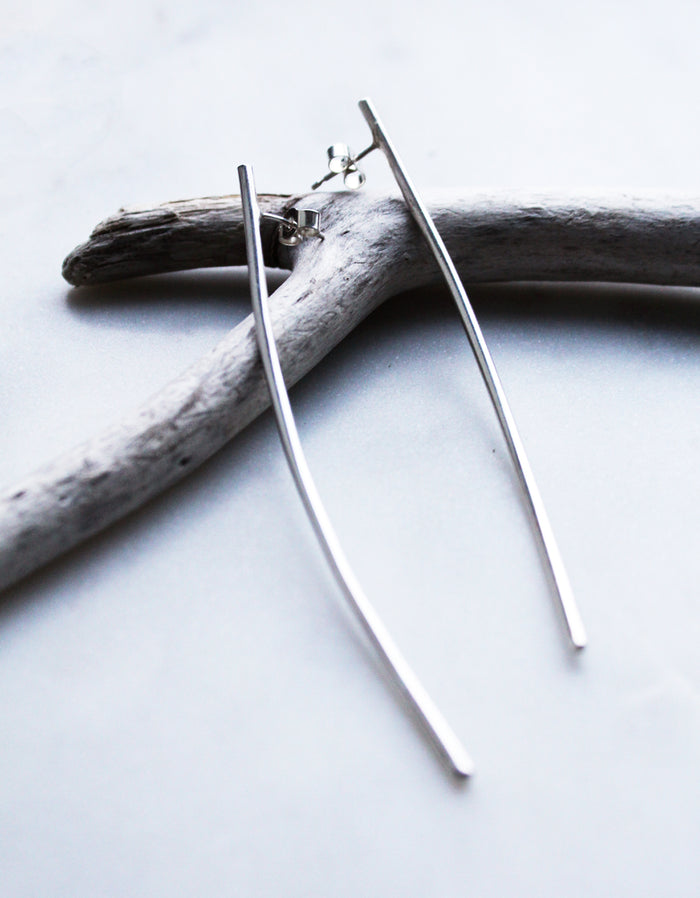 Curve earrings by M of Copenhagen flatlay on drift wood