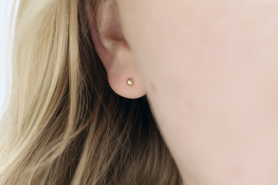 Dew drop bead earrings in recycled gold by M of Copenhagen on model