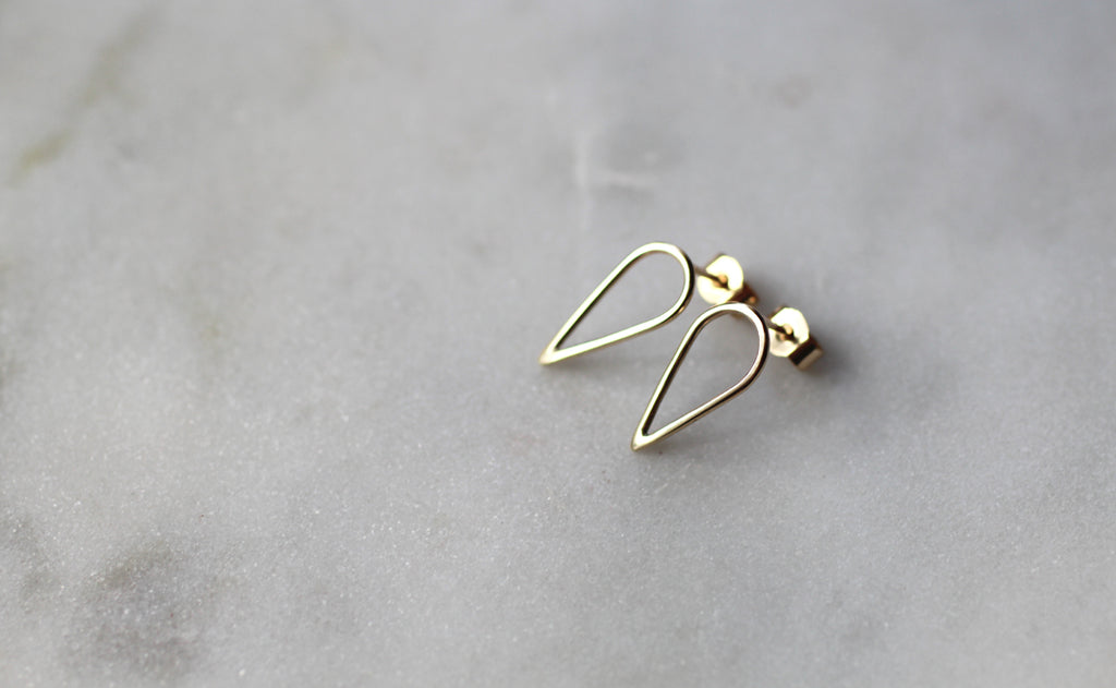 Filippa Arrow in 9 ct recycled gold by eco jeweller M of Copenahgen on marble