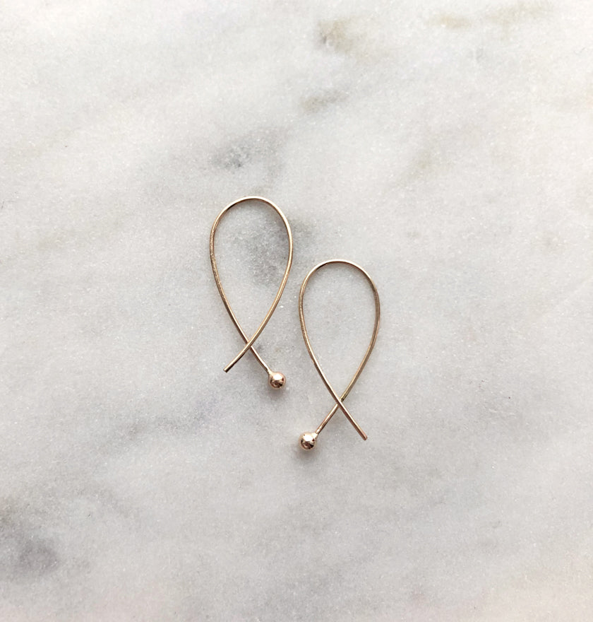 Gabrielle Cross over gold earrings by eco jeweller M of Copenhagen placed on marble from front