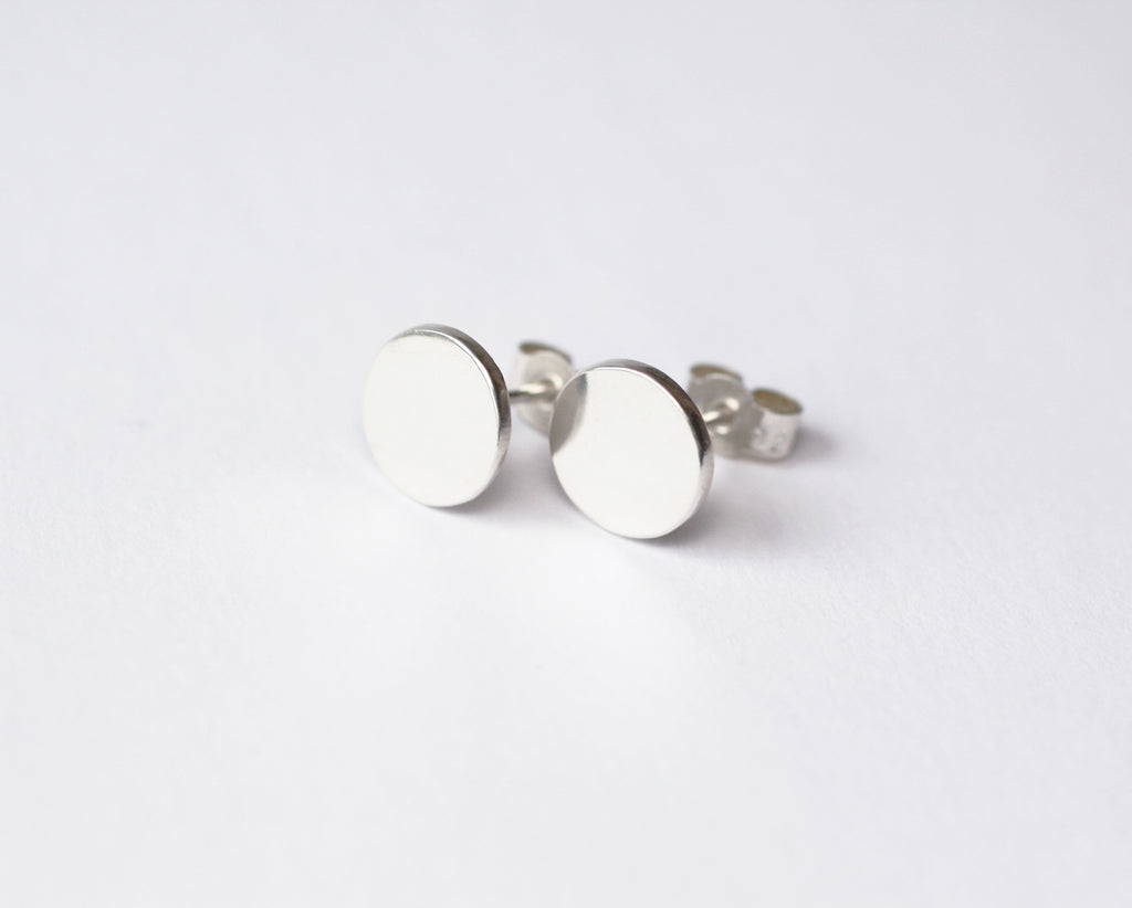 Moon earrings by M of Copenhagen with mirror finish placed on white background