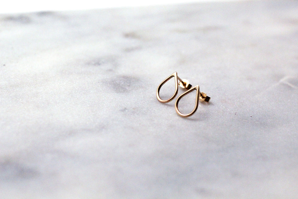 Recycled 9 ct yellow gold Filippa Mini earrings by eco jeweller M of Copenhagen laid out on marble