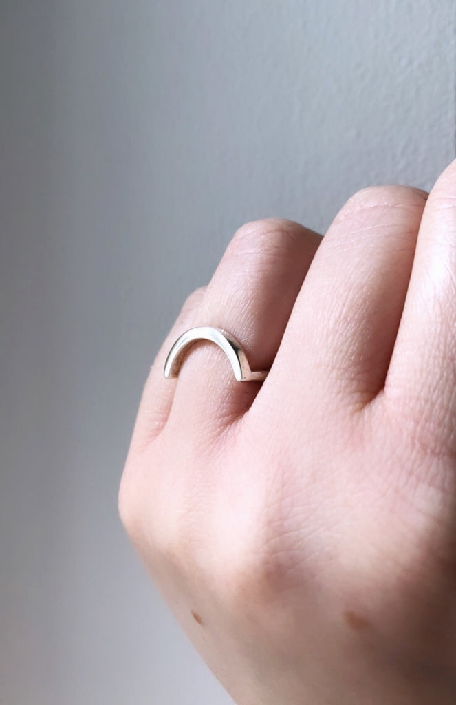 Uno unisex curved U shaped ring in recycled silver by M of Copenhagen on models hand