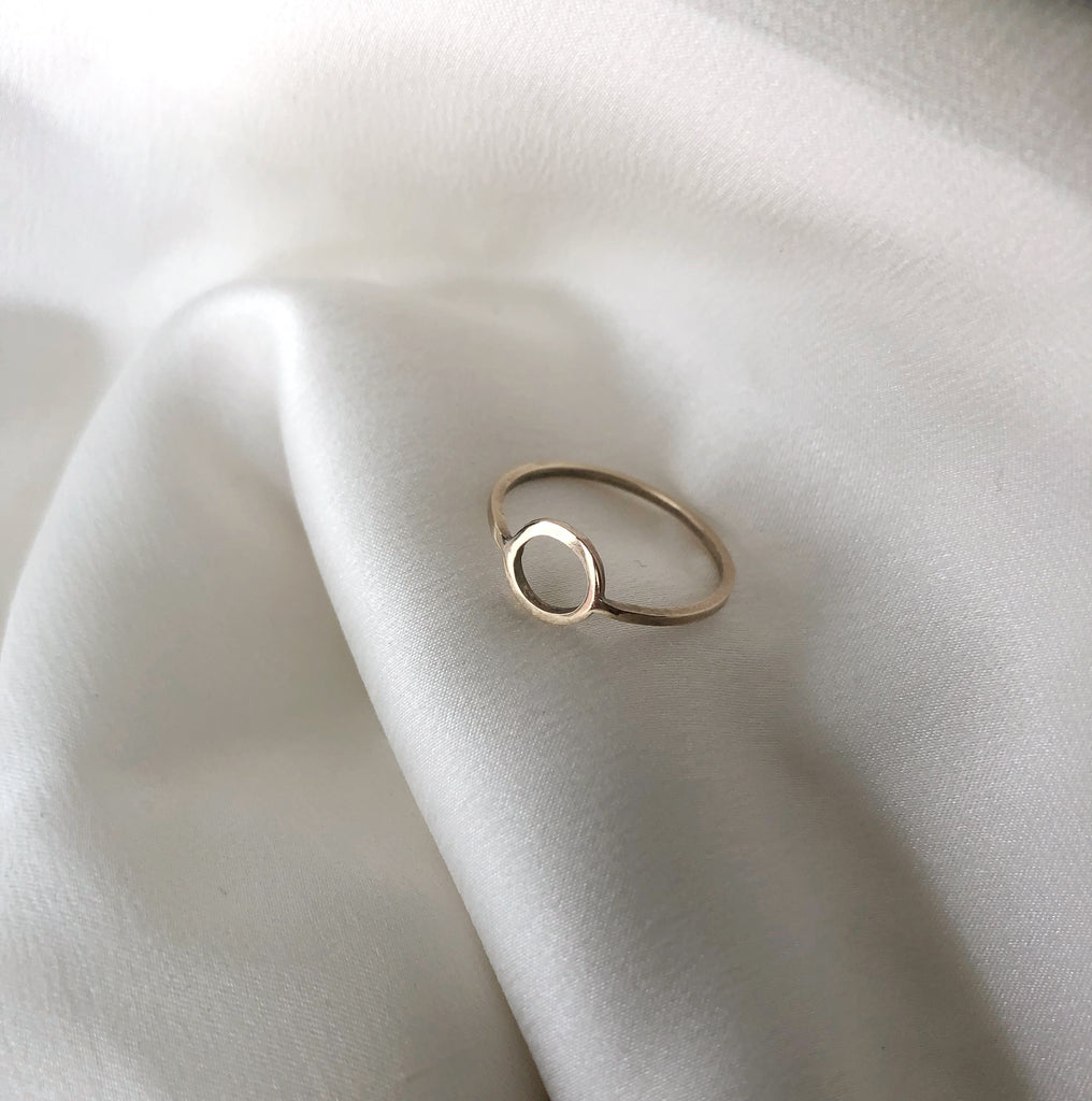 golden circle ring by M of Copenhagen on white silk background