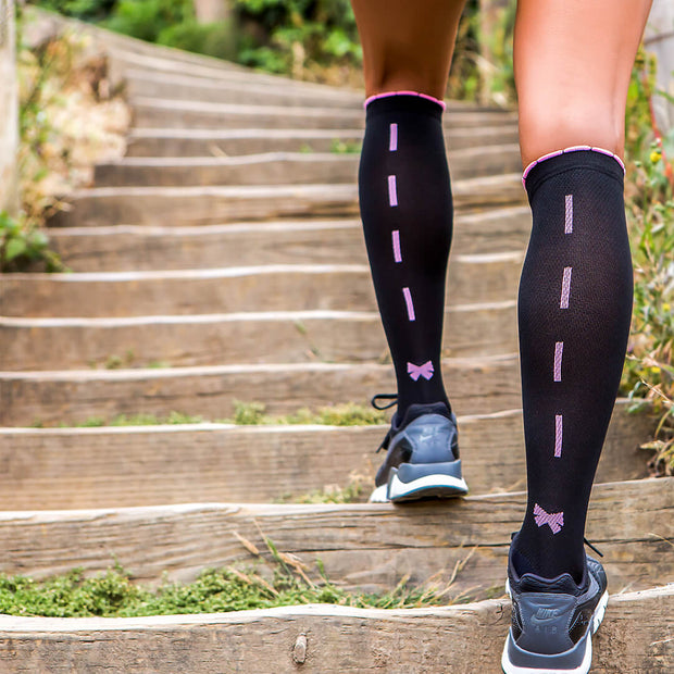Elegant and sleek black designer compression socks for runners with sexy pink ribbon and bow down the back