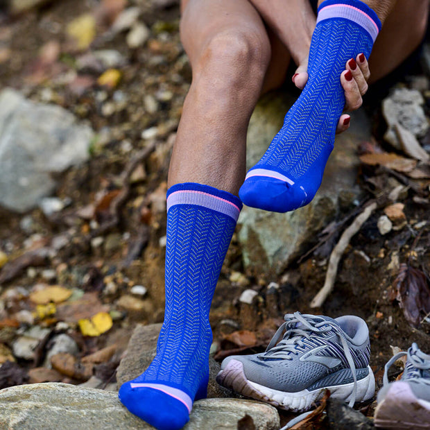 Runner resting in compression crew socks in blue herringbone
