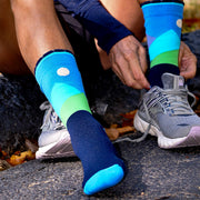 Close-up of runner putting shoe on over blue compression crew socks with moonlit mountains design