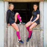 Two athletes sitting, wearing hot pink polka dotted compression, one in calf sleeves and the other in socks
