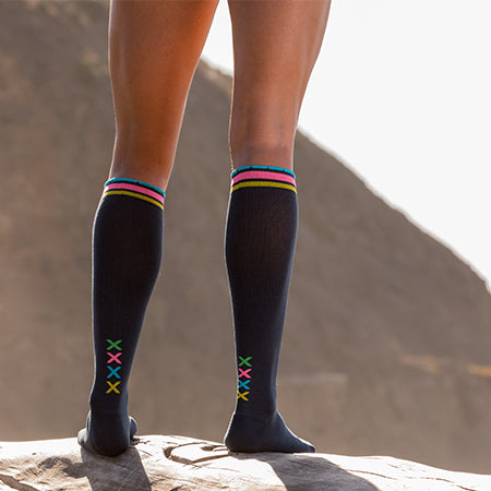 Close-up of athlete legs wearing slate compression socks with vertical multi-colored XXXX at ankles