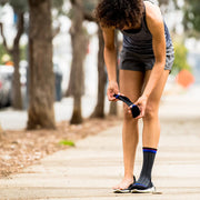 Woman putting on black herringbone  compression crew socks