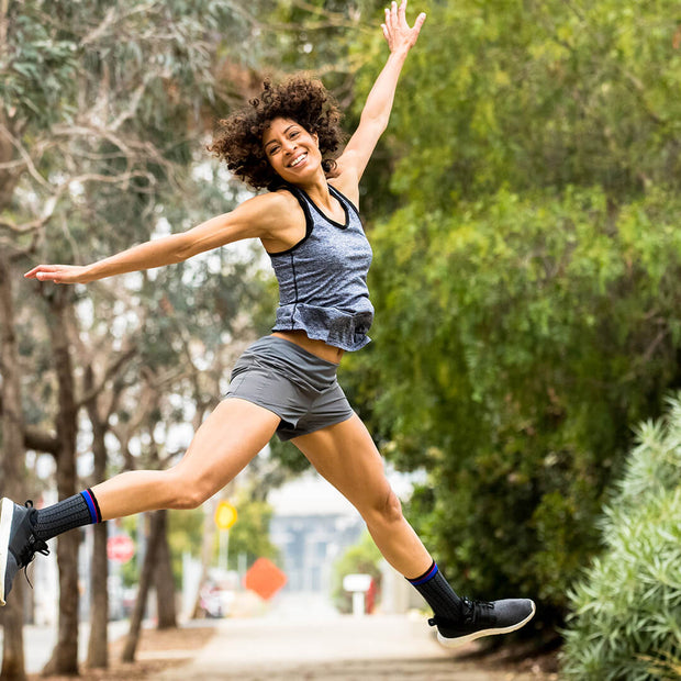 Woman leaping in black herringbone  compression crew socks