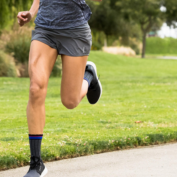 Running legs wearing black herringbone  compression crew socks