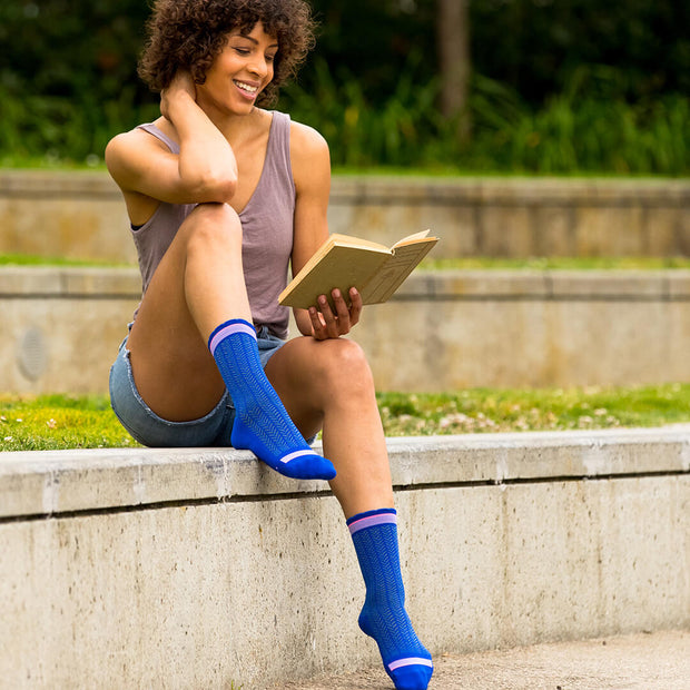 Woman reading & wearing blue herringbone compression crew socks
