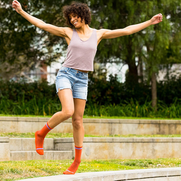 Woman dancing in orange herringbone compression crew socks