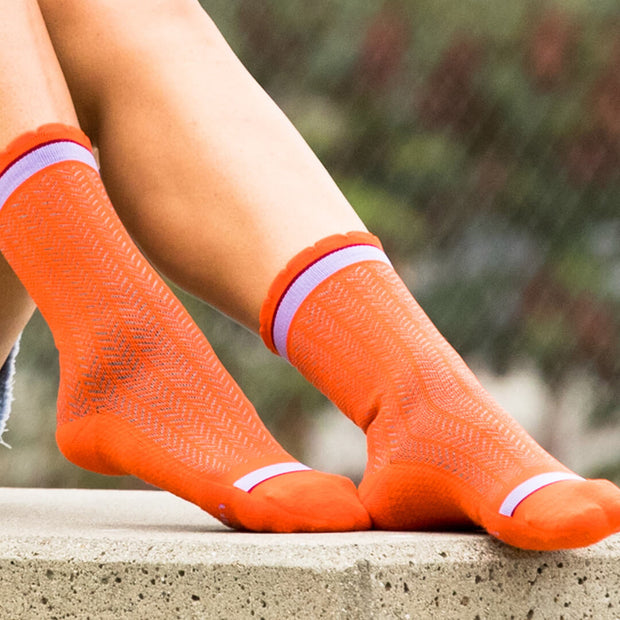 Close-up of feet in orange herringbone compression crew socks