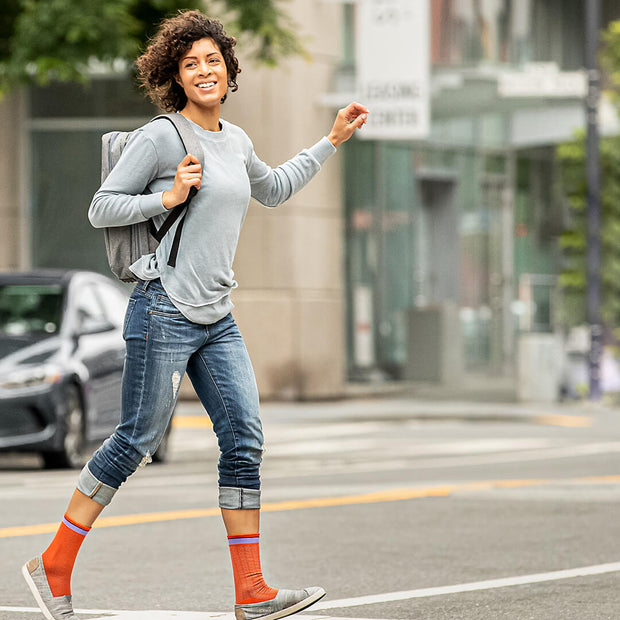 City woman with backpack walking in orange herringbone compression crew socks