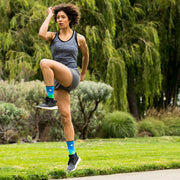Woman exercising outdoors in blue compression crew socks with moonlit mountains design
