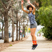 Happy woman jumping with arms in the air wearing orange compression crew socks featuring moonlit mountains design