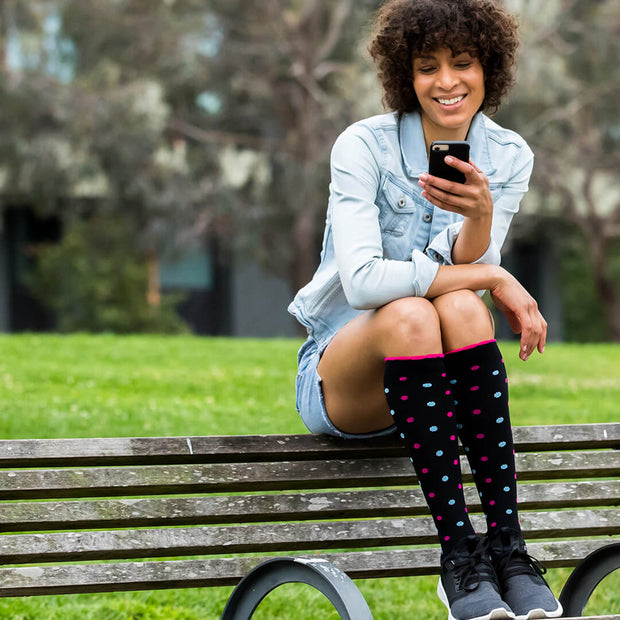 Woman on park bench wearing black compression socks with pink and light blue dots