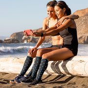 Two runners taking a selfie break, wearing slate compression socks with blue and mint polka dots