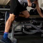 Male legs in weight room wearing blue herringbone compression crew socks