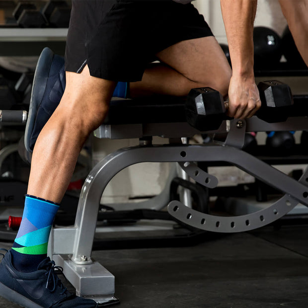 Man lifting in weight room wearing blue compression crew socks featuring moonlit mountaintops
