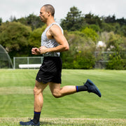 Man running & wearing black herringbone compression crew socks