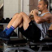 Man working out in weight room wearing blue herringbone compression crew socks