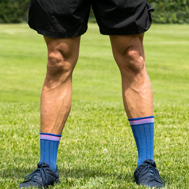 Male athlete legs wearing blue herringbone compression crew socks