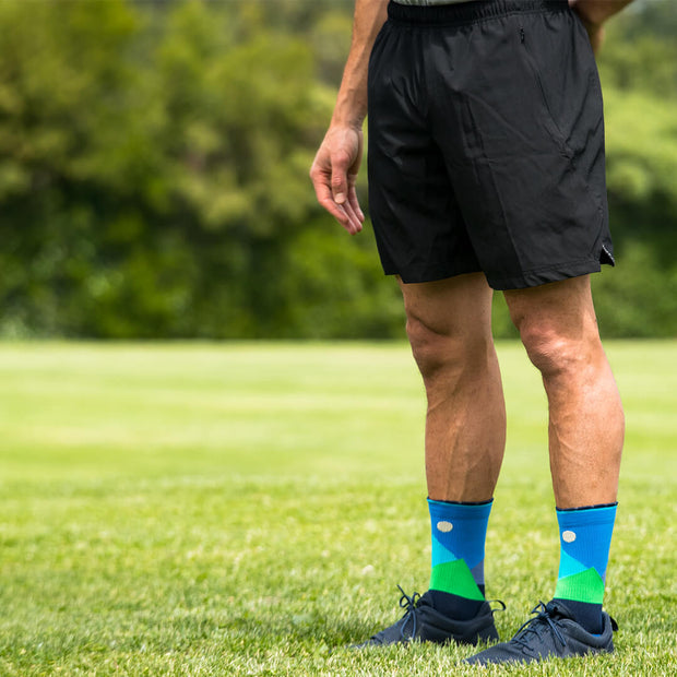 Male athlete in field wearing blue compression crew socks featuring moonlit mountaintops