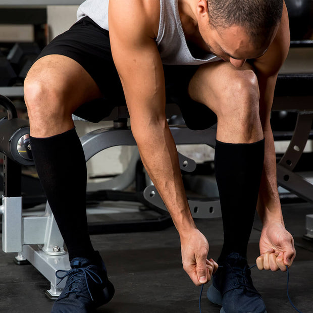Man in weight room wearing solid black compression socks