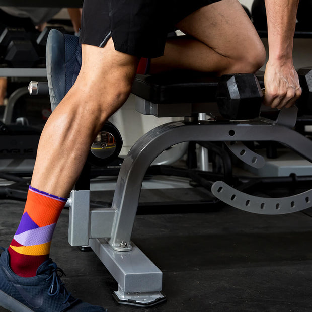 Male legs in weight room wearing orange compression crew socks featuring moonlit mountaintops