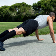 Man in plank position wearing solid black compression socks