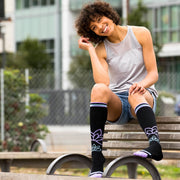 Smiling woman on park bench wearing black compression socks with lotus flowers and light blue & purple accents