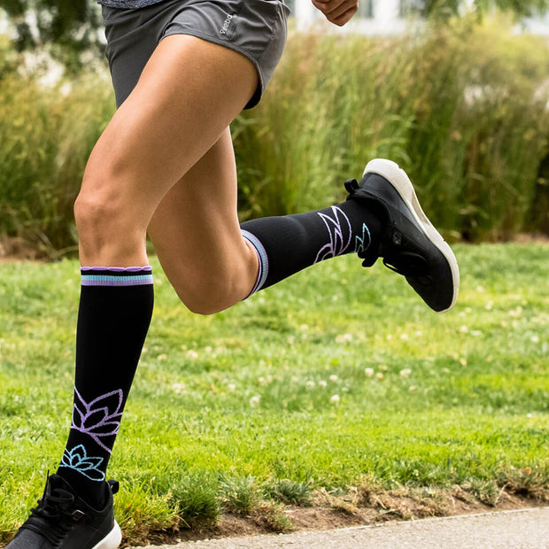 Close-up of runner's legs wearing black compression socks with lotus flowers and light blue & purple accents