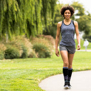 Woman walking & wearing black compression socks with lotus flowers and light blue & purple accents